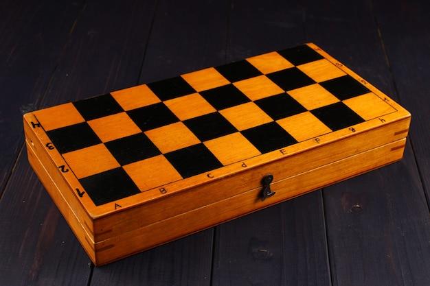 Scatola degli scacchi su una superficie di legno scuro