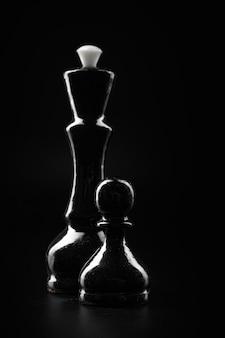 Figure di scacchi su sfondo nero scuro si chiudono