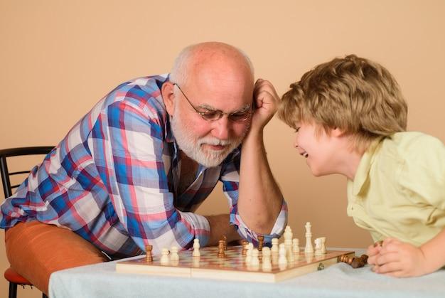 Bambino di scacchi che gioca a scacchi con il nonno nonno che insegna al nipote a giocare a scacchi relazione familiare