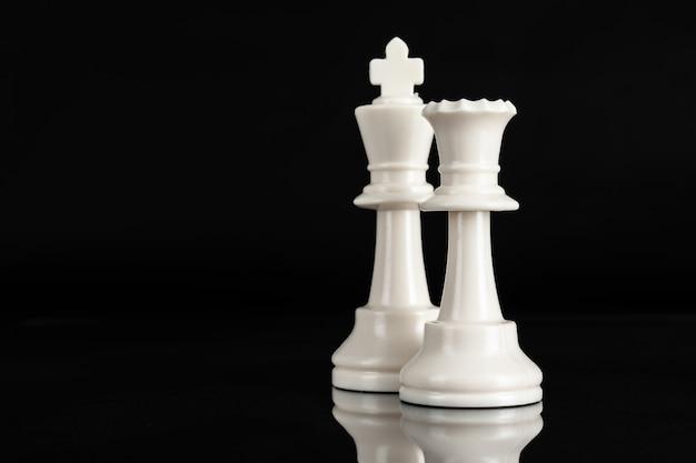 Pezzo degli scacchi da vicino su sfondo nero. concetto di leadership