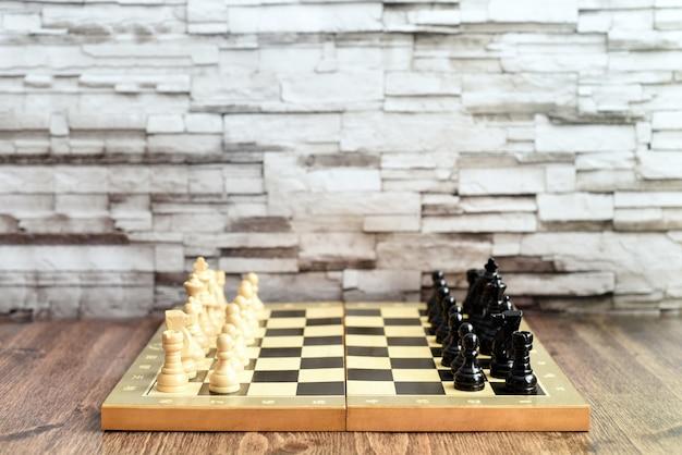 Pezzi degli scacchi sulla scacchiera sul tavolo di legno. sfondo sfocato con copia spazio