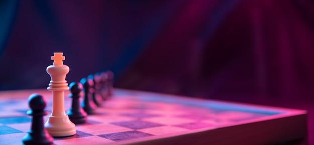 Pezzi degli scacchi su una scacchiera su uno sfondo scuro girato in colori neon rosa-blu. la figura di uno scacchi. primo piano.