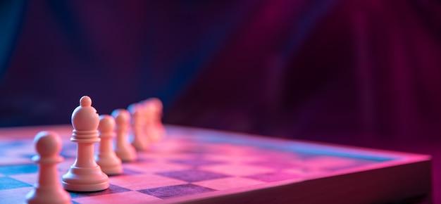 Pezzi degli scacchi su una scacchiera su uno sfondo scuro girato in colori neon rosa-blu. la figura di scacchi. primo piano.