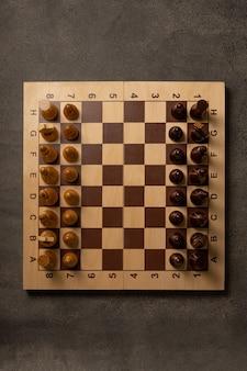 Pezzi degli scacchi su una scacchiera su uno sfondo scuro