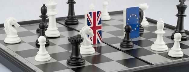 Pezzi degli scacchi e bandiere dell'unione europea e della gran bretagna su una scacchiera gioco politico