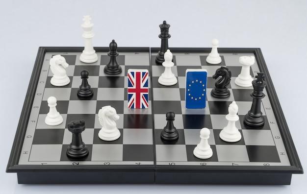 Pezzi degli scacchi e bandiere dell'unione europea e della gran bretagna sulla scacchiera gioco politico