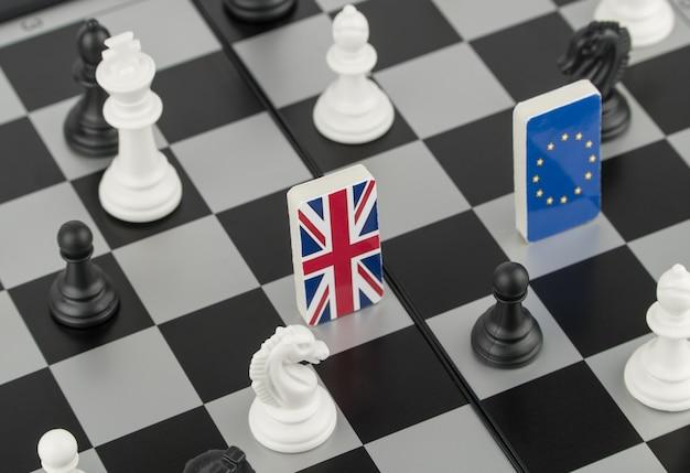Pezzi degli scacchi e bandiere dell'unione europea e della gran bretagna su una scacchiera