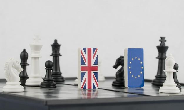 Pezzi degli scacchi e bandiere dell'unione europea e del regno unito su una scacchiera gioco politico