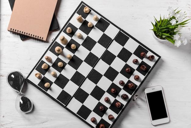 Pezzi degli scacchi con tabellone e clessidra sul tavolo bianco