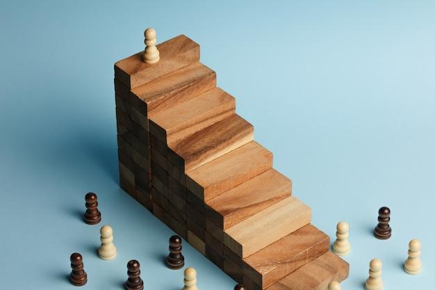 Scacchi in piedi su una piramide di blocchi di legno. concetto di scala di carriera, gerarchia aziendale con spazio di copia.