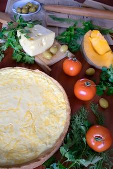 Torta al forno di formaggio, pomodori, zucca, verdure sulla tavola di legno. mix di verdure, cibo fresco vegetariano vegano, cucina casalinga.