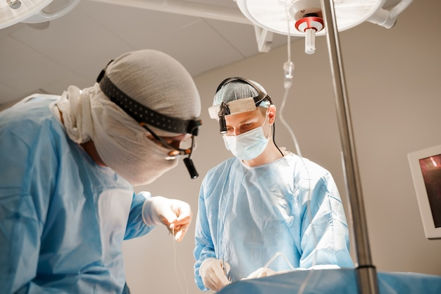 Operazione plastica di aumento del torace e correzione in clinica medica. il chirurgo inserisce l'impianto in silicone nel petto della donna.
