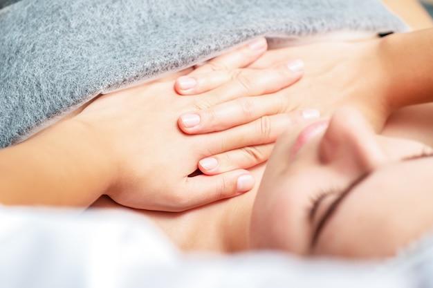 Massaggio toracico della donna dalle mani del massaggiatore si chiuda.