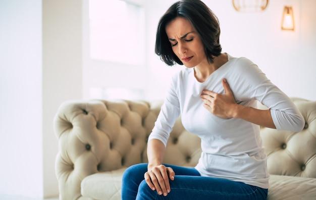 Dolore al petto. foto ravvicinata di una ragazza bruna seduta su un divano con gli occhi chiusi e la mano sinistra che si tocca la zona del cuore.