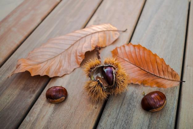 Castagne e foglie secche su piano in legno