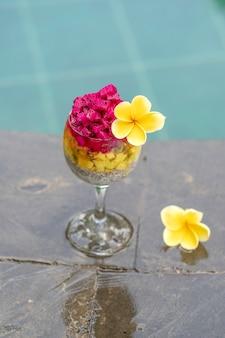 Budino di semi di chia con frutto del drago rosso, frutto della passione, mango e avocado in un bicchiere per colazione sullo sfondo dell'acqua della piscina, primo piano. il concetto di una sana alimentazione.