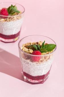 Budino alla vaniglia con semi di chia, lampone, avena, musli e menta su rosa, ombra dura, foto di alta qualità