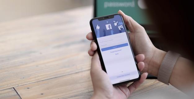 Chiang mai ,thailandia 24 ago 2021: donna in possesso di un iphone x con servizio internet sociale facebook sullo schermo.