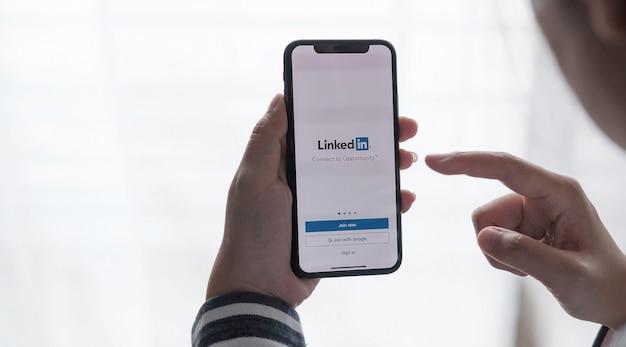 Chiang mai, thailandia, lug c12, 2021: una donna tiene in mano apple iphone xs con l'applicazione linkedin sullo schermo. linkedin è un'app per la condivisione di foto per smartphone.