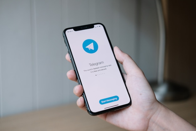 Chiang mai, thailandia, 22 giugno 2020: mano della donna che tiene iphone x con il servizio di social network telegram sullo schermo. iphone 10 è stato creato e sviluppato da apple inc.