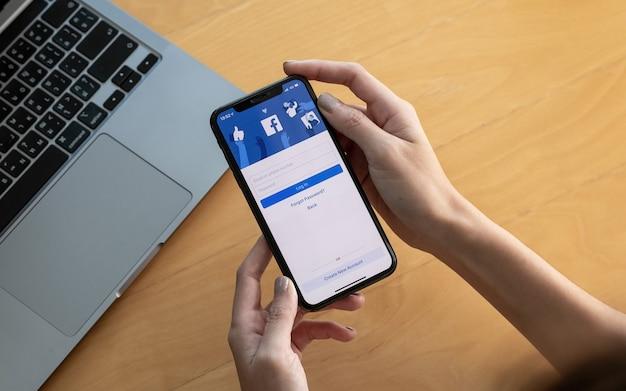Chiang mai, thailandia - 3 ottobre 2018: logo dell'app social media facebook al login, pagina di registrazione dell'iscrizione sullo schermo dell'app mobile su iphone x (10) nella mano della persona che lavora su attività di shopping e-commerce.