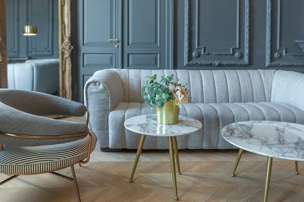 Interni chic della stanza in stile rinascimentale del xix secolo con mobili di lusso moderni. le pareti di nobile colore scuro sono decorate con stucchi e cornici dorate, parquet in legno.