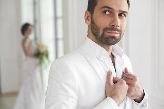 Sposa e sposo chic sposi in posa in uno studio bianco. coppia felice ridendo. vestito bianco. abito bianco. gioventù. nozze. lampadario. divano. la porta. Foto Premium