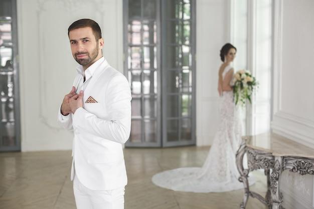 Elegante sposi sposo e sposa in posa in uno studio bianco. risata felice delle coppie. vestito bianco. abito bianco. gioventù. nozze. lampadario. divano. la porta.
