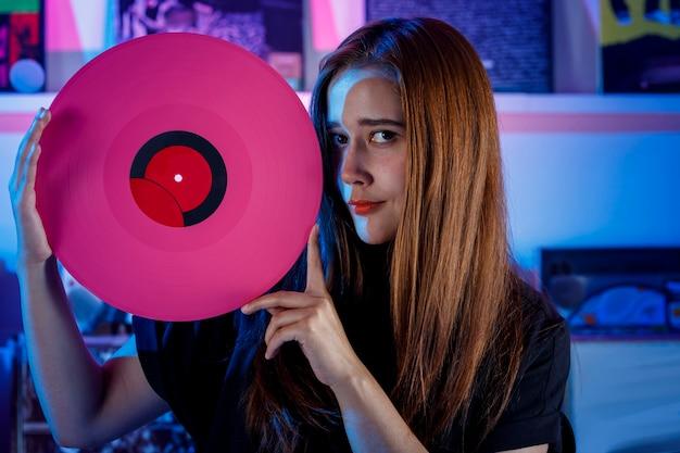 Chica latina sosteniendo un disco de vinilo en sus manos concepto de chica dj en tienda de discos