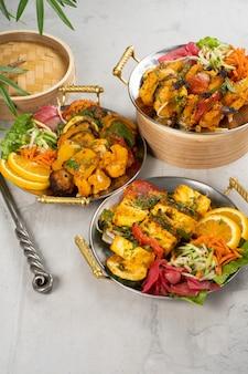 Spiedini di pollo, manzo e maiale con contorno di verdure e spezie piccanti, cucinati in tandoor. un set di tre piatti di carne calda in piatti tradizionali indiani.