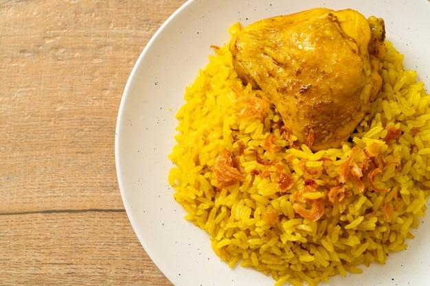 Biryani di pollo o riso al curry e pollo - versione tailandese-musulmana del biryani indiano, con riso giallo profumato e pollo - stile alimentare musulmano