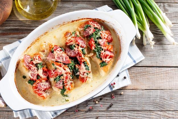 Petto di pollo in salsa cremosa all'aglio in teglia su un tavolo di legno. cibo dietetico sano. vista dall'alto, distesi, copia spazio