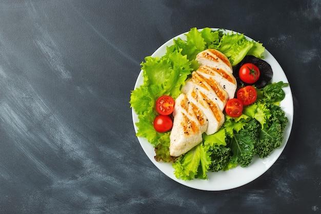 Filetto di petto di pollo e insalata di verdure con pomodori e foglie verdi. il concetto di cibo sano e dieta keto. vista dall'alto.