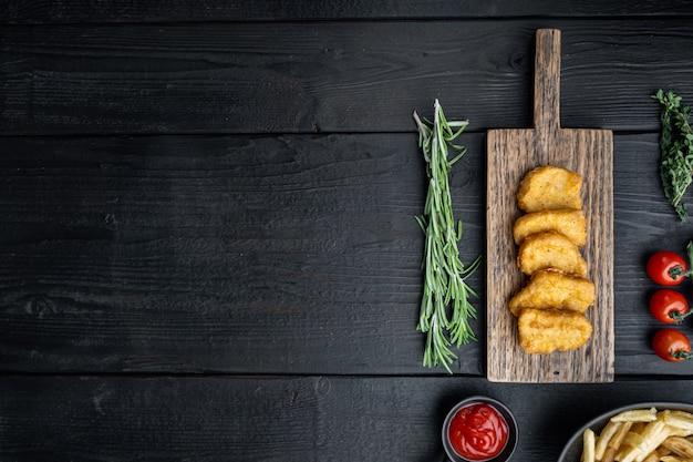 Pepite di petto di pollo fritte sulla tavola di legno nera