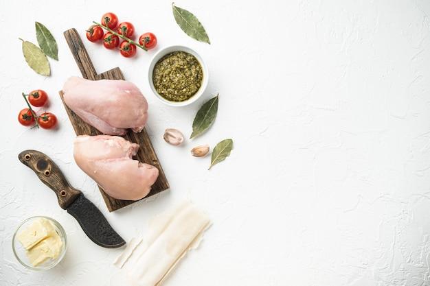 Petto di pollo farcito con ingredienti e set filo, su pietra bianca