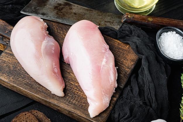 Petti di pollo con coltello da macellaio sulla tavola di legno nera