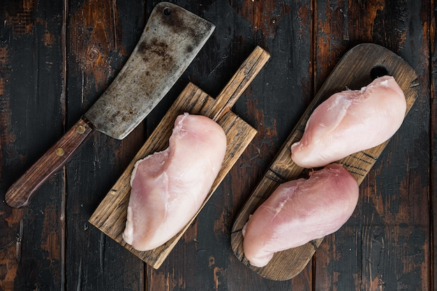 Petti di pollo con coltello da macellaio, sul tavolo di legno scuro, piatto laici