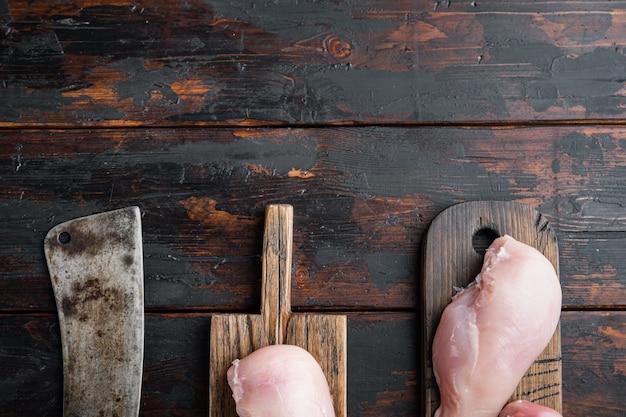 Petti di pollo con coltello da macellaio, sul tavolo di legno scuro, vista dall'alto
