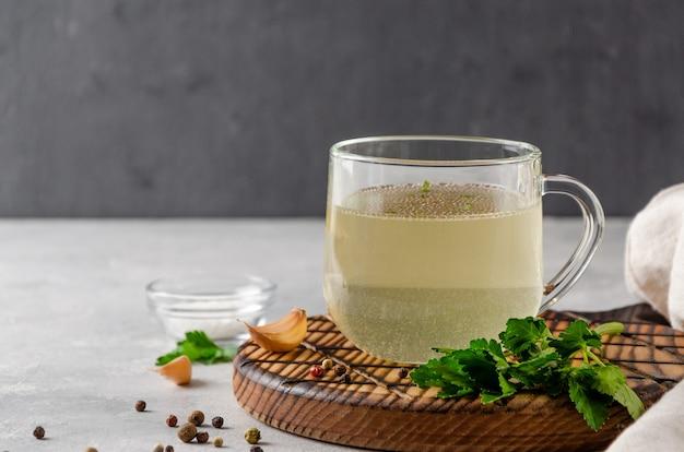 Brodo di pollo in una tazza di vetro con prezzemolo, aglio e altre spezie su vassoio di legno su sfondo grigio