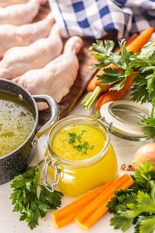 Brodo di pollo in un barattolo di vetro cosce di pollo crudo carota cipolla sedano erbe aglio e verdure fresche.