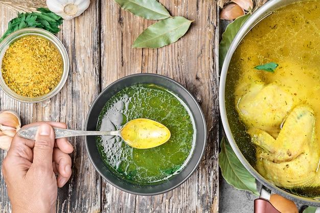 Brodo di pollo in un piatto sul tavolo, la mano della ragazza tiene un cucchiaio, una casseruola con la zuppa e gli ingredienti per la zuppa su un tavolo di legno