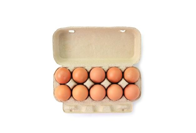 Uova di pollo marrone in scatola di cartone su bianco