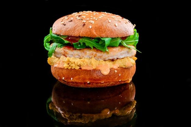 Hamburger di pollo con salsa di formaggio e pomodoro su una superficie nera