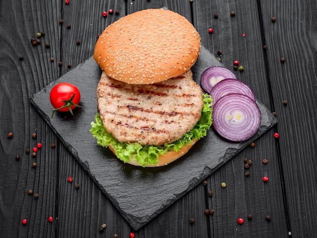 Hamburger di pollo con pomodori, lattuga e salsa su superficie nera ardesia