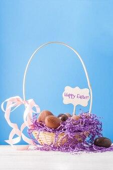 Pollo, uova di cioccolato, cestino decorativo di carta viola