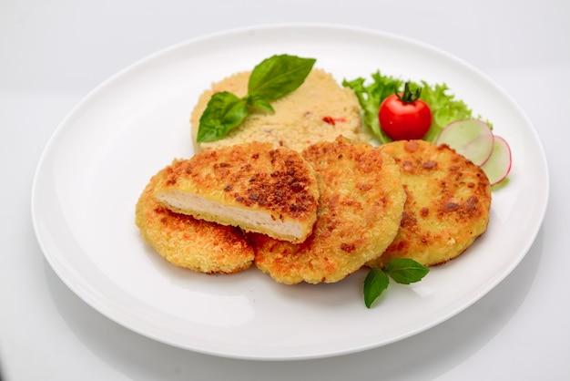 Cotoletta di pollo in pastella con bulgur su sfondo bianco
