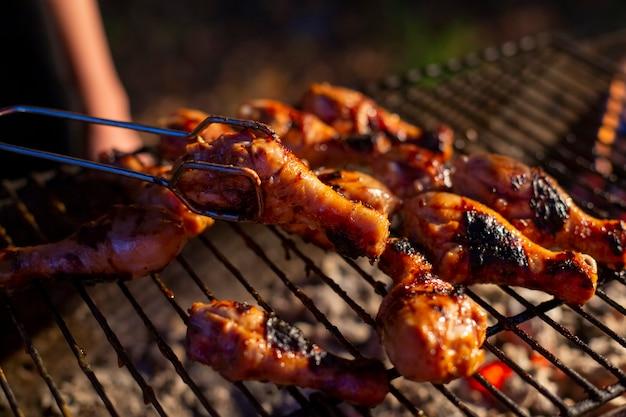 La sera le cosce di pollo vengono grigliate su un barbecue