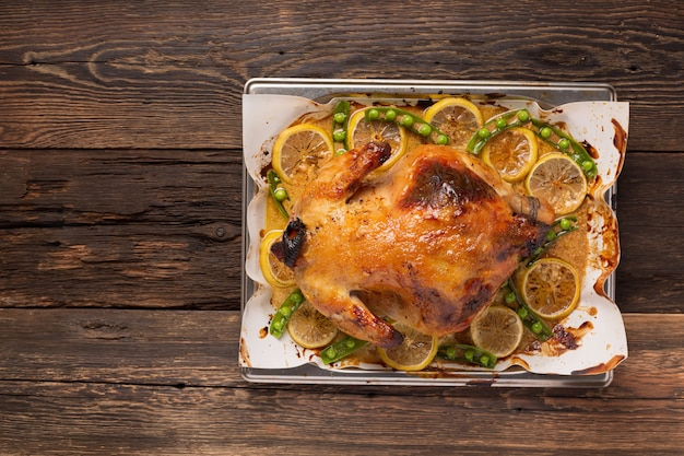 Pollo o anatra al forno sul tavolo da pranzo festivo