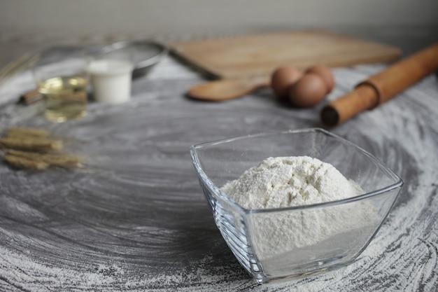 Uovo di gallina, farina, olio d'oliva, latte, spighe di grano, utensile da cucina su sfondo grigio tavolo.