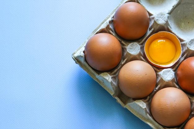 L'uovo di gallina è rotto a metà tra le altre uova uova marroni e tuorlo d'uovo sullo sfondo blu vista dall'alto